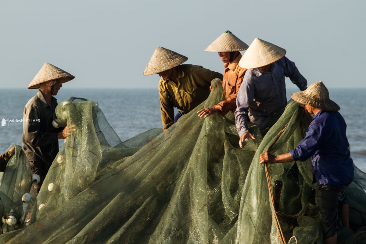 Fishermen in conical hats pulling net