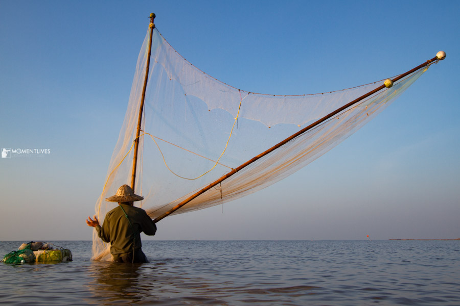 A fisherman scooping fish at the sea side of Nam Dinh