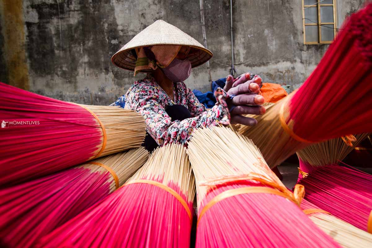 A lady drying incense on our Hanoi photo tours