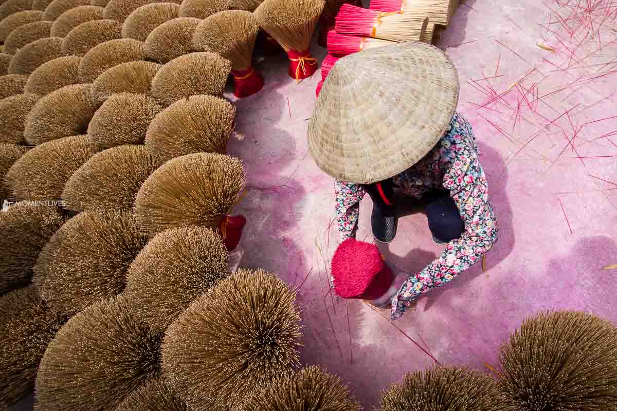 Photo of a lady arranging incense in the yard