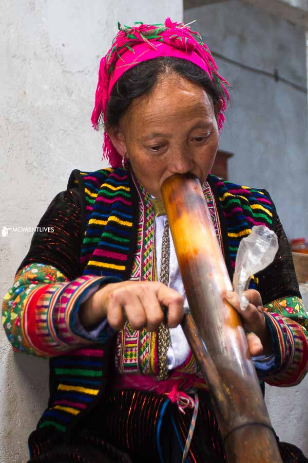 A woman smoking tobacco in the market of Ha Giang